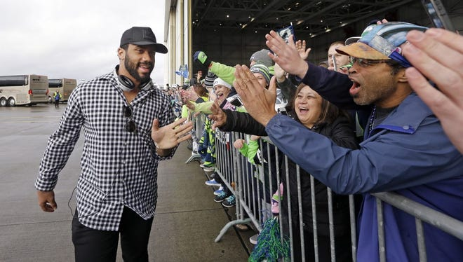 Seattle Seahawks quarterback Russell Wilson greets airline employees and their families Monday on the team's return from the Super Bowl at Seattle-Tacoma International Airport in SeaTac, Wash. The Seahawks lost in the Super Bowl to the New England Patriots on Sunday.