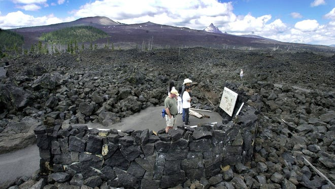A vast expanse of barren rock from an ancient lava flow surrounds visitors to the lava flow interpretive site on the McKenzie Highway.