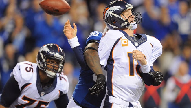 FILE - Denver Broncos' Peyton Manning (18) has the ball knocked away by Indianapolis Colts' Robert Mathis (98) during the first half of Sunday night's game at Lucas Oil Stadium on October 20, 2013. Matt Detrich / The Star