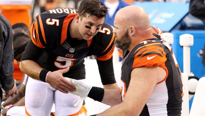 Bengals quarterback AJ McCarron talks with tackle Andrew Whitworth during a game late last season.