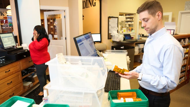 Chris Harlow, pharmacist and owner of St. Matthews Community Pharmacy, fills prescription orders Wednesday. Harlow is leading the way in a growing movement to allow pharmacists to dispense naloxone, a heroin antidote, to loved ones of addicts without them having a doctor's prescription.