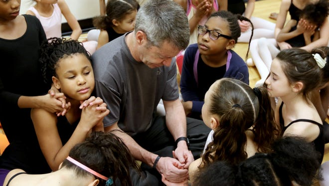 Gordon Havens, director of the Princesses Ballet, prays with his students during practice.