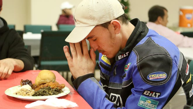 Ryne Davis prays before eating a free meal provided by the Nehemiah Project on Thursday at Holy Trinity Church in Dover.