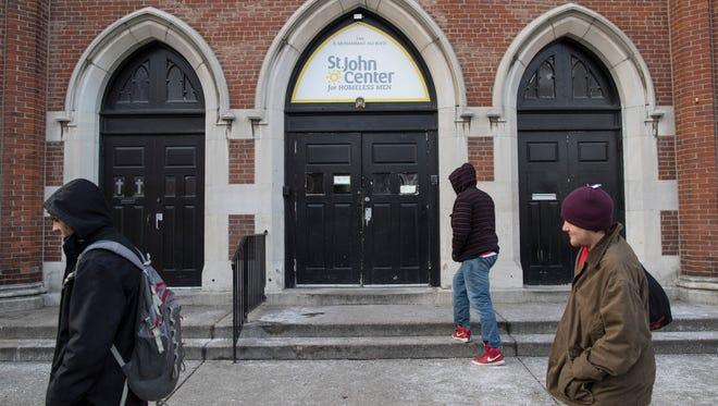 Men who are homeless walk outside the St. John Center for Homeless Men on Feb. 13, 2018.