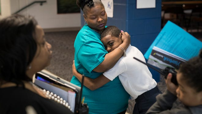 Foster Traditional Academy family resource center coordinator, Latascha Craig, gets a hug from student Daquayle Mckinney on Monday. April 23, 2018