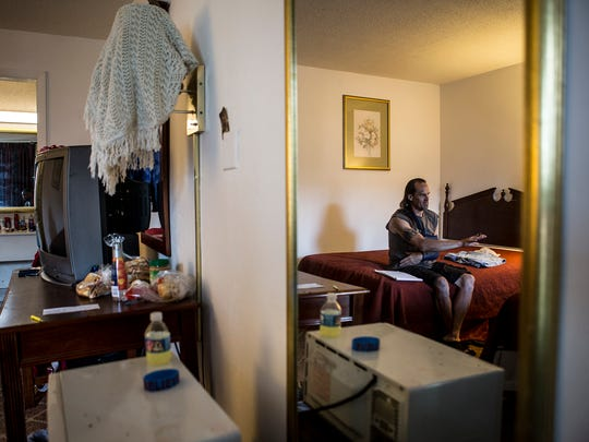 Tim Bixler sits on a bed in a motel room at the Knights Inn, in Heath, where he and his partner, Janine Horne, recently moved.