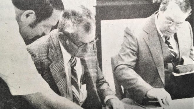 Columbia County's Jake Ivey (from left), Dillard Watkins and U.H. PIttman look over courthouse repair figures during a 1979 meeting.