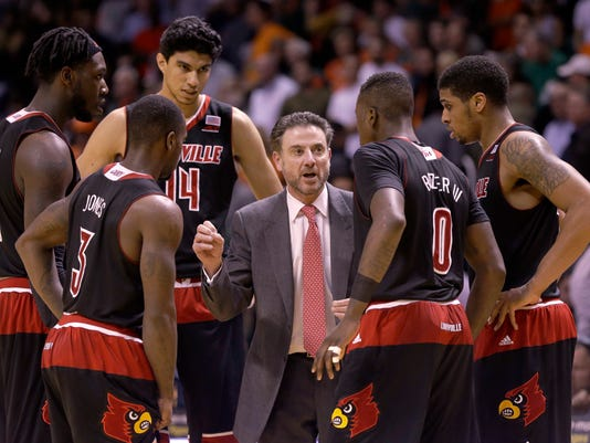 Louisville head coach Rick Pitino, center, talks to players during a time out in the second half of an NCAA college basketball game against Miami, Tuesday, Feb. 3, 2015, in Coral Gables, Fla. Louisville defeated Miami 63-55. (AP Photo/Wilfredo Lee),