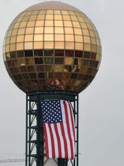 An American flag hangs from the Sunsphere in downtown Knoxville, displayed correctly: flat, with the Union on the left. The 266-foot steel tower topped with a five-story gold globe, was built for the 1982 World's Fair.