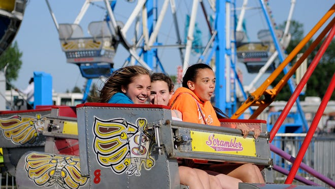 Girls laugh as they're spun around on the Scrambler at the 35th annual Walleye Festival on Friday.