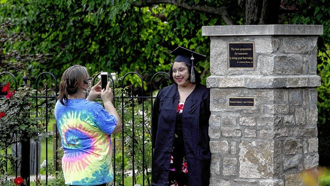 Erica Gonzales takes a photo of her daughter, Carolina, 17, in her graduation regalia June 1 at the Park of Roses. The senior picked up her cap and gown earlier that day and will graduate June 24 from Columbus Alternative High School.