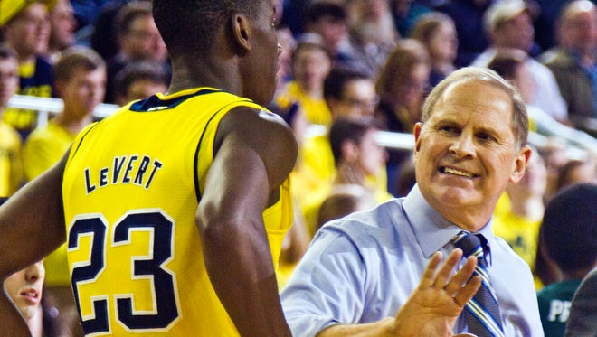 Michigan basketball coach John Beilein, right, gives instructions to guard Caris LeVert on Dec. 9, 2014.