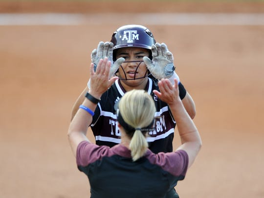 Texas A&M's Tori Vidales (8) high fives Texas A&M coach