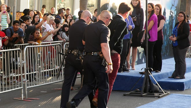 "A fan is walked off carpet in handcuffs after allegedly attacking Brad Pitt at the world premiere of ""Maleficent"" at the El Capitan Theatre on Wednesday, in Los Angeles."