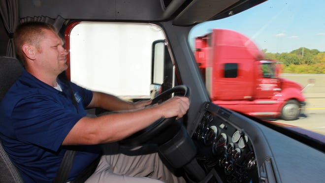 Another tractor trailer passes Craig Hammons, driver manager for Verst Group Logistics, as he drives a Frieightliner tractor trailer on Interstate 75 in Northern Kentucky. Hammons, of Dry Ridge, drove a truck for 10 years before moving into his current position.
