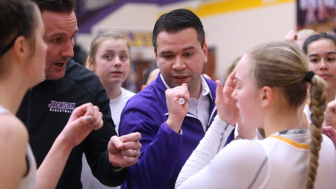 Jackson girls basketball coach Anthony Butch (center) talks to his team during a sectional final last year against Lake.