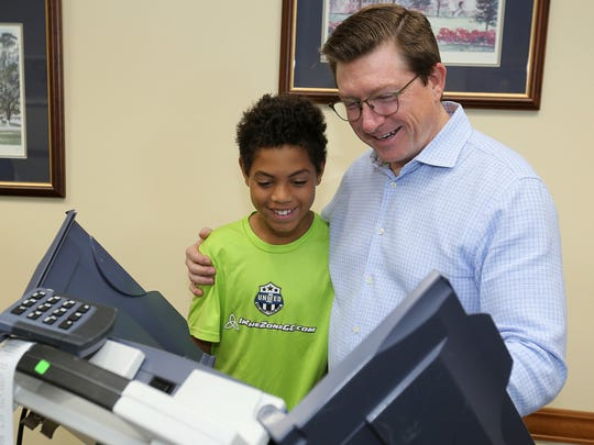 Max Baria, 10, watches as his father, State Rep. David Baria, votes on Tuesday, June 5, 2018 at the Hancock County Library in Bay St. Louis, Miss. Baria came in second in the the Democratic primary for Republican U.S. Senator Roger Wicker's seat. He'll face venture capitalist Howard Sherman in the primary runoff on Tuesday.(John Fitzhugh/The Sun Herald via AP)