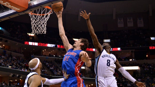 Boban Marjanovic shoots between Grizzlies guard Vince Carter, left, and forward James Ennis III in the first half of the Pistons' 103-90 win Sunday, April 9, 2017 in Memphis, Tenn.