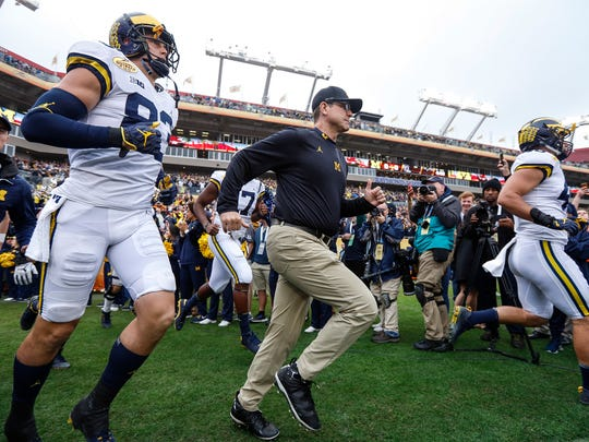 Michigan Wolverines head coach Jim Harbaugh and players
