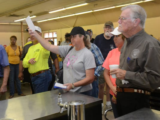 ANI Coliseum Auction Laronda Howard bids on a bar cooler at the Rapides Parish Coliseum auction held Saturday. Howard got the bar cooler which she said they plan to use as counter space in a shop.-Melinda Martinez/The Town Talk