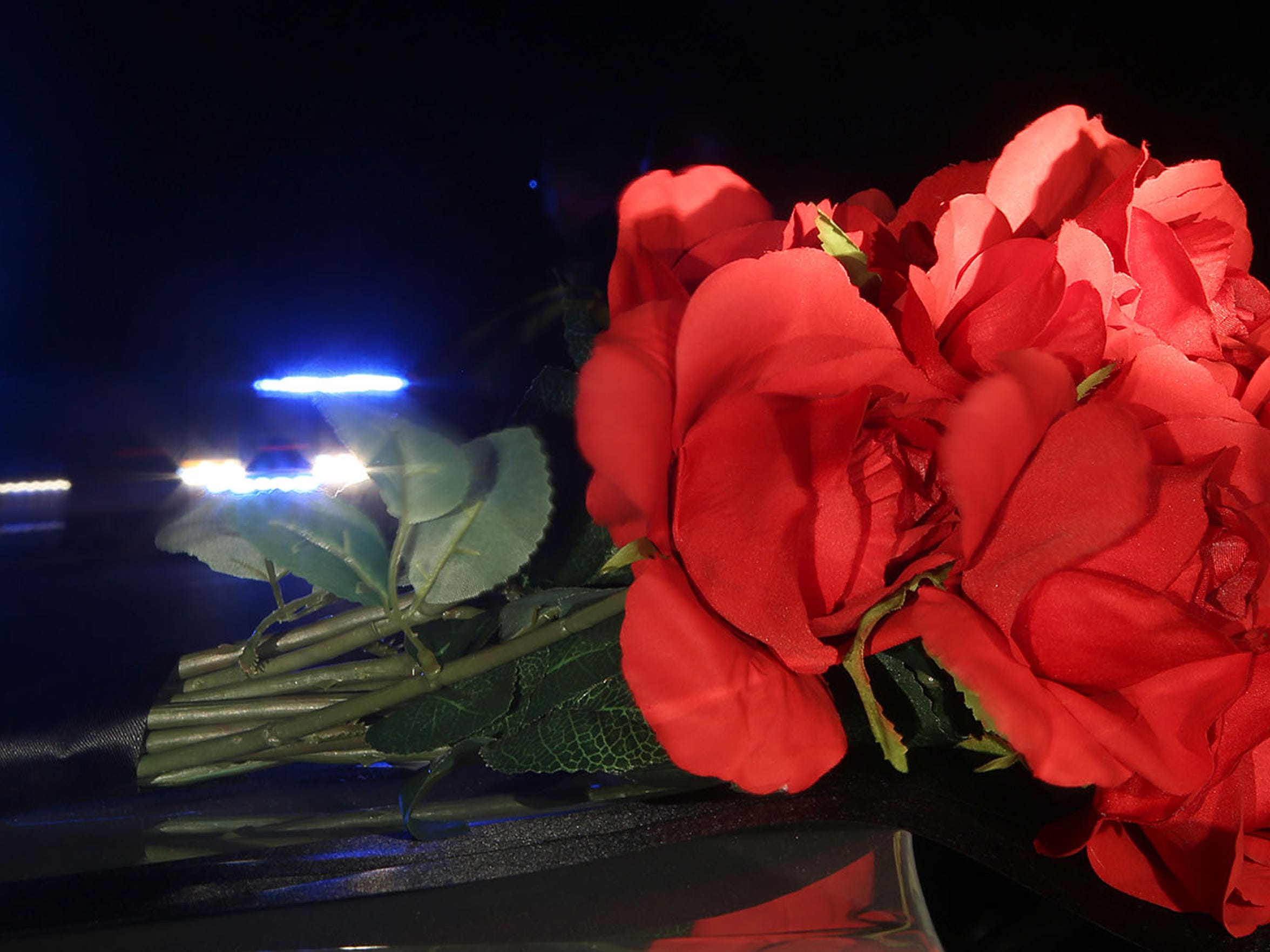 As the Sea of Blue passes by, flowers are seen Thursday on the hood of a police vehicle along U.S. Highway 70, where Madison County Sheriff's Deputy Rosemary Vela died in a single-car crash Monday night.
