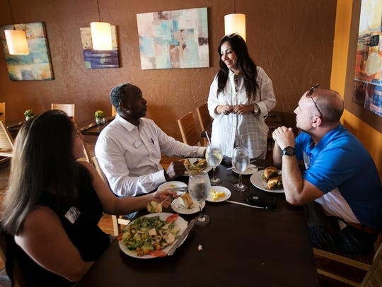 Gloria Jordan, standing, interacts with customers,