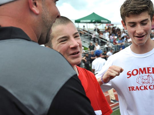 """John """"Spo"""" Esposito (c) enjoys a laugh with coach Mike Sokolofsky (l), teammate Greg Fusco (r) and others after running the 100 at the Westchester County Track & Field Championships."""