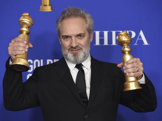 """Sam Mendes poses in the press room with the awards for best director, motion picture and best motion picture drama for """"1917"""" Sunday at the 77th annual Golden Globe Awards."""