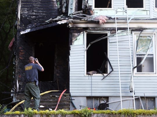 A Morris County Sheriffs investigator takes photos go the aftermath of a two-family home on Chestnut Street in Morristown was destroyed early Friday morning, the occupants got out safely but six pets were feared to have perished in the fire. June 10, 2016, Morristown, NJ