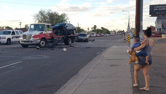 A woman involved in a Maryvale car crash on Sept. 28, 2016, watches as crews clean up of accident. None of the six people involved was seriously injured.