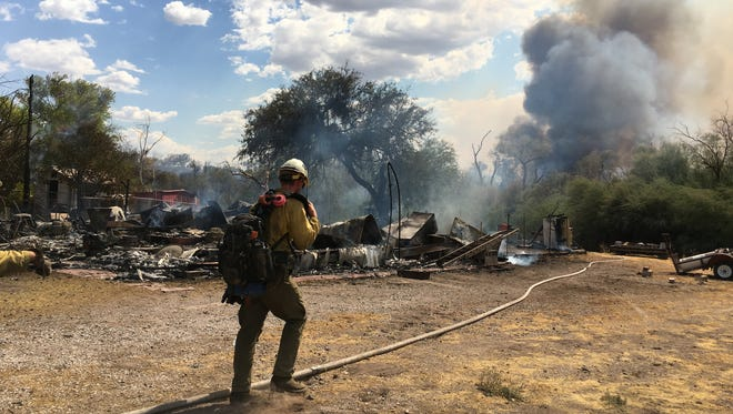A fire fighter battles the Roach Fire in Pinal County. The fire destroyed three homes and seven other structures in Dudleyville.