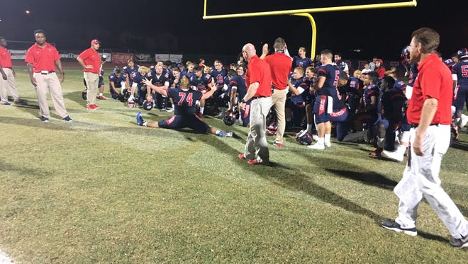 Centennial players and coaches celebrate after beating Chaparral to advance in the Arizona high school footbal playoffs.