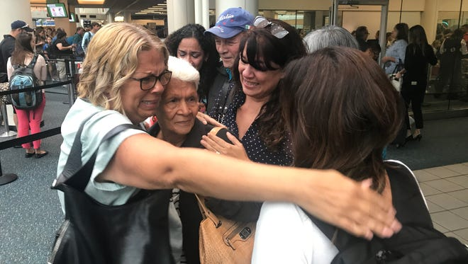 Leonor Figueroa, 82, center, a survivor of Hurricane Maria, is surrounded by her daughters after arriving at the Orlando airport from Puerto Rico in September.