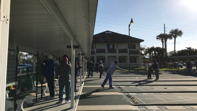 Dotty Koert of Spanish Lakes and originally from Ontario, takes a shot at the shuffleboard courts in Vero Beach Jan. 18, 2018,  despite temperatures in the 30s.