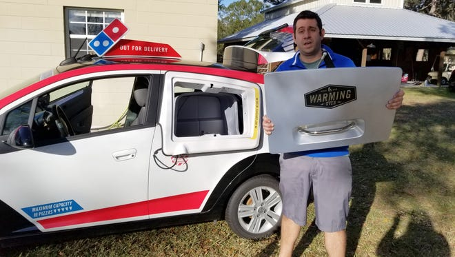 YouTube personality known as Samcrac is facing a potential legal threat from Domino's Pizza. He is with the Domino's Pizza delivery car that he bought at an auction and repaired.