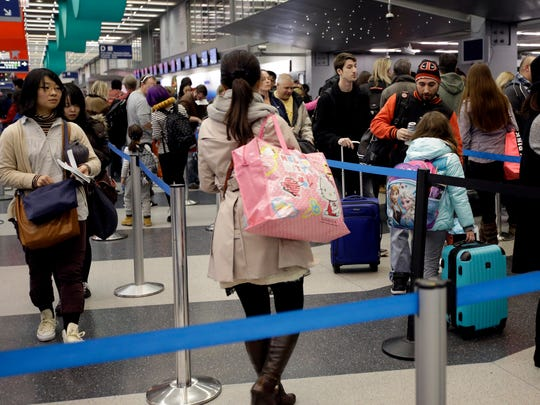 Travelers line up at a security checkpoint area  Dec.