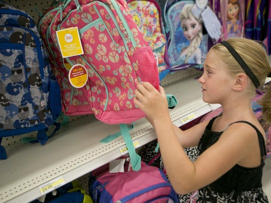 Brehna Buffington, 7, of Marshfield looks at backpacks in the back to school section at Target in Marshfield, Monday, July 20, 2015.