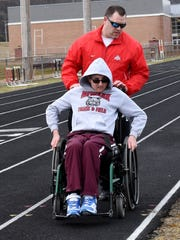 Coach Mat Dunham helps Braedon Pollmann during warm ups for Newark's unified track team, which pairs students with Special Olympics participants.