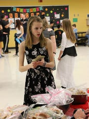 Hailey Constantineau, a member of the carnival planning committee, looks at the baked goods for sale at the Whitnall Carnival for dysautonomia May 5.
