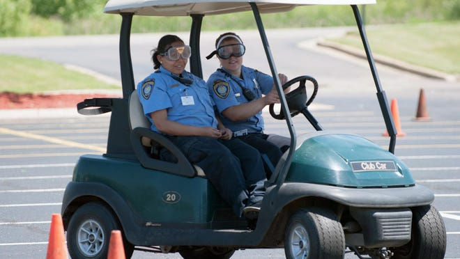 """BCPD cadets Mariah Martin, left, and Lynette Fuller practice the driving course while wearing the """"drunk"""" goggles."""