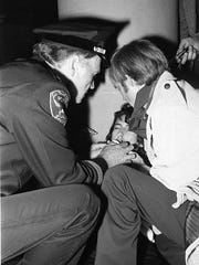 San Francisco Supervisor Carol Ruth Silver was hit in the mouth by a rock thrown by a rioter as she emerged from San Francisco City Hall. At left, Police Chief Charles Gain and an unidentified person administer first aid. Rioting began after a peaceful parade by the gay community erupted into a rock throwing, car burning, looting fiasco.