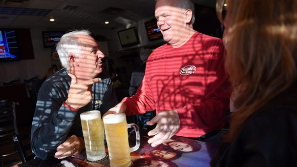 Jon Bot (center) owner of Botski's Bar and Grill delivers beers to Steve (left) and and Stacy LeBoutillier during happy hour on Friday. LeBoutillier and Bot have been friends since high school.