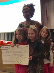Students at Brandywine Springs School present a check to Amina Capaldi, founder of Wish Them Well, to dig a well in Togo.