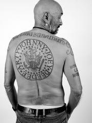 The late Arturo Vega displays a back tattoo of The