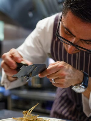 Chef Vincenzo from Osteria Tulia, shaving truffles on a dish.