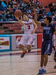 Aztec's Gabe Wood makes layup around Window Rock's Adrian Destea on Thursday at the Chieftain Pit in Shiprock.