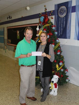 Shown is David Land of Mobile Exxon as he presents a check to Principal Shanon Lusk of Walhalla Elementary School for STEM projects.