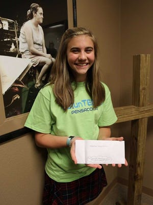 Claire Jimenez, 14, stands with a $1,000 check for Waterfront Rescue Mission. She and her friends raised the money to help feed the hungry and homeless at Thanksgiving.