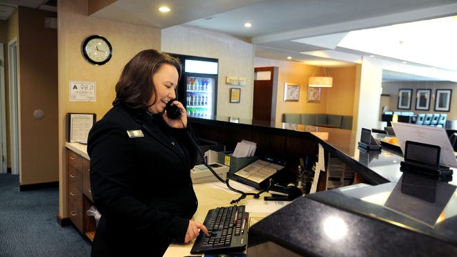 Marci Anderson answers the phone at the front desk of Residence Inn Asheville Biltmore on Wednesday. Anderson is a Western Carolina University student working toward a bachelor's degree in hospitality and tourism.