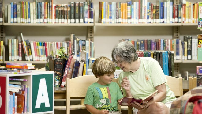 Maggie Winn reads a story to her grandson, Wayah Stone, 3, at the East Asheville library on Wednesday. The library is well used and in need of renovation or expansion.